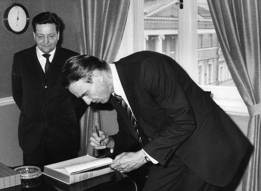 Pääministeri Mauno Koivisto kirjoitti Juhla-Kalevalan luovutuksessa nimikirjoituksensa teoksen kansilehdelle vuonna 1981. Kuvassa myös kirjan luovuttanut Tampereen Kirjapaino Oy:n toimitusjohtaja Timo Laatunen.