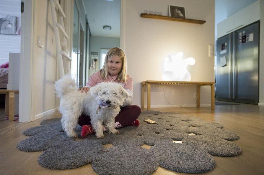 Nella ja Roosa-koira ovat hyviä kavereita. Eteistä valaisee Eero Aarnion suunnittelema lamppu, joka on sijoitettu Artekin ritiläpenkin päälle.