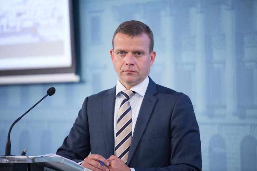 Valtiovarainministeri Petteri Orpo (kok.) ihmettelee juhlarahan kuvaa.