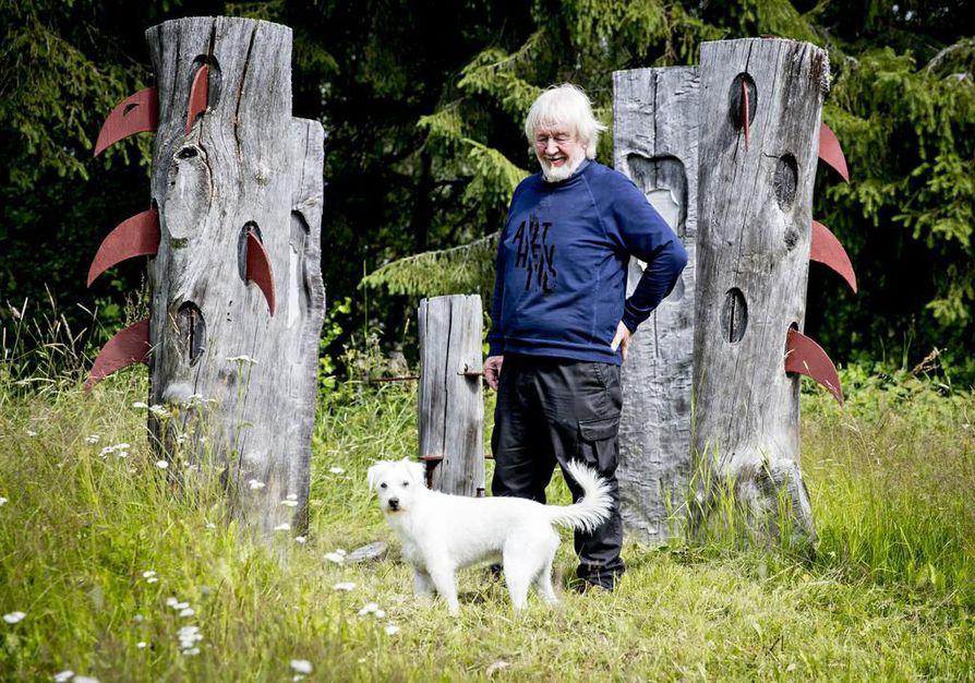 """""""Veistospuisto säilyy Saarelassa edelleen, ja pyrin hoitamaan sitä Hiukkavaarasta käsin"""", Erkki Halvari kertoo esitellessään Jaffa-terrierin kanssa gallerian pihapiirissä olevia teoksia. Puhuvat puut -teokseen Halvari on käyttänyt Mauri-myrskyn Kemijärvellä kaatamaa honkaa."""