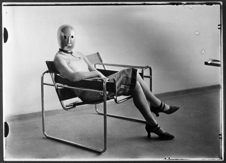 Tämä Erich Consemüllerin ottama kuva on yksi kuuluisimpia Bauhaus-koulussa otetuista valokuvista. Bauhaus uudisti tuotekuvausta. Kukaan ei tiedä, kuka kuvassa naamioituneena esiintyvä nainen on.