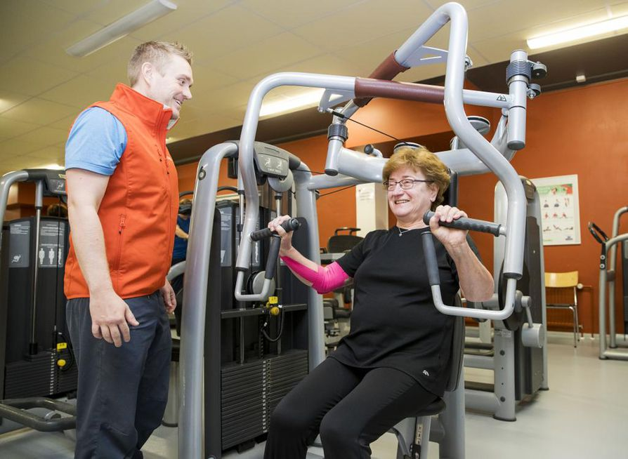 """Liikunnanohjaaja Tommi Laine tarkistaa, että Vuokko Nyman ei """"lintsaa"""" vaan tekee liikkeet tehokkaasti."""
