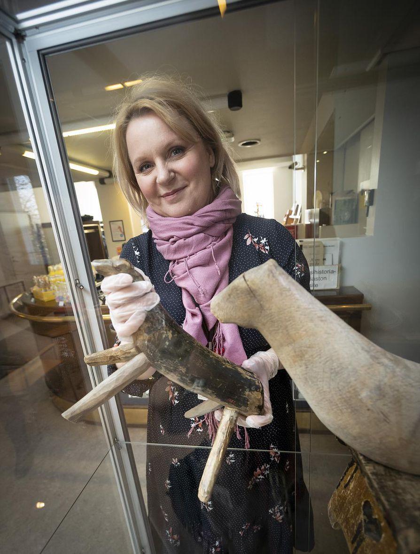 Riina Kohonen esittelee näyttelyn vanhimpia puuhevosia 1800-luvulta. Pienempi hevonen on Kuusamosta, isompi Pudasjärveltä.