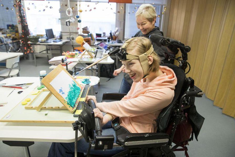 Heini Peltomäki käy 9. luokkaa Tervaväylän koulun Lohipadon yksikössä. Hän innostui maalaamisesta viime kesänä, ja sen jälkeen pensseli on viuhunut. Ohjaaja Riitta Vilppola seuraa vierestä, kun Peltomäki maalaa pääkypärän avulla.