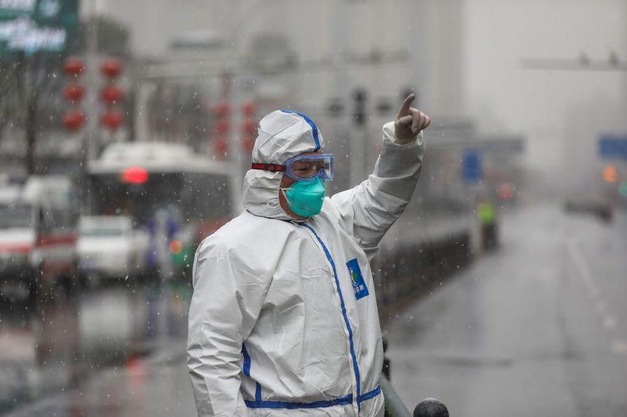 Mies ohjasi autoilijaa Kiinan Wuhanissa koronaviruksen saaneiden potilaiden hoitamiseen tarkoitetun sairaalan edustalla.