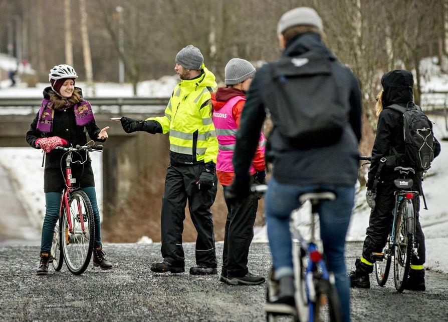 Kirsikka Lehtiniemi saa Harri Vaaralalta valon pyöräänsä. Linnanmaan baanan päätepisteessä oli hetkittäin ruuhkaa, kun Oulun kaupunki jakoi led-valoja pyöräilijöille.