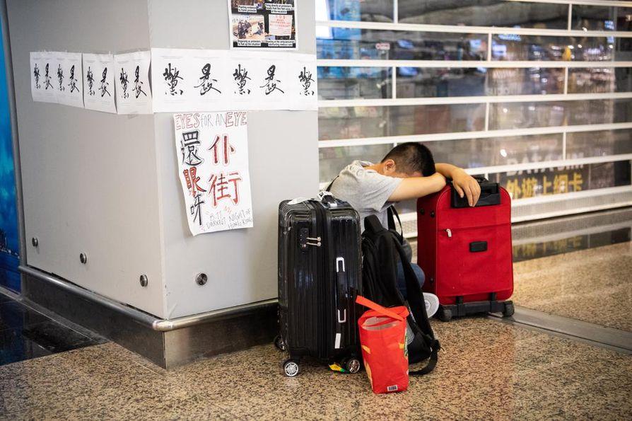 Väsyneet matkustajat odottivat lennolle pääsyä Hongkongin lentoasemalla maanantaina. Lentoasema on matkustajamäärältään maailman kahdeksanneksi vilkkain.