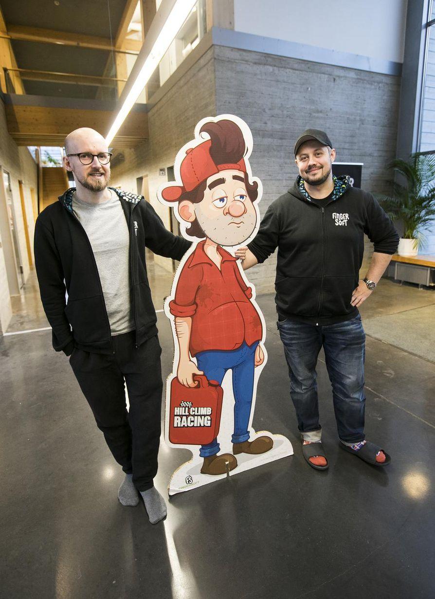 Fingersoftin art director Tuomas Soukka (vas.) ja Apaja-pelikampuksen toiminnasta vastaava Daniel Fischer ovat tottuneet poseeraamaan Hill Climb Racing -pelistä tutun pahvisen Bill Newtonin kanssa.