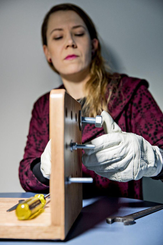 Kirsi Jussila esittelee SmartPro-hankkeessa kehitettyjä hanskoja. Tällä laitteella testataan hanskojen näppäryyttä esimerkiksi mutterien kiinnityksessä ja löysäämisessä.