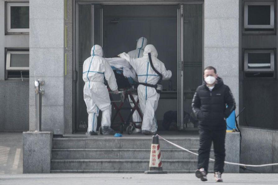 Sairaalan henkilökunta kantoi potilasta Jinyintanin sairaalaan Kiinan Wuhanissa, jossa leviää uudentyyppinen, hengenvaarallinen koronavirus.