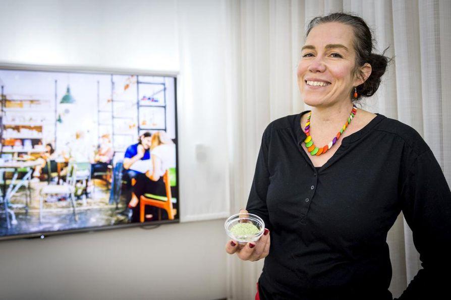 Mari Sandell esittelee mustaviinimarjajauhetta moniaistihuoneessa, jossa tutkitaan, miten eri aistit vaikuttavat ruokailuun. Tilassa on kuvaseinä, eri väreissä valaiseva lamppu ja tuoksulaite.