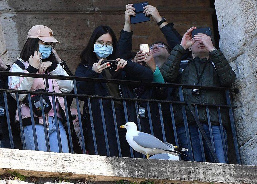 Roomassa keskiviikkona nähtävyyksiä katselleet turistit suojautuivat virukselta hengityssuojaimilla. Italia vahvisti keskiviikkona, että 12. ihminen oli kuollut koronavirukseen.