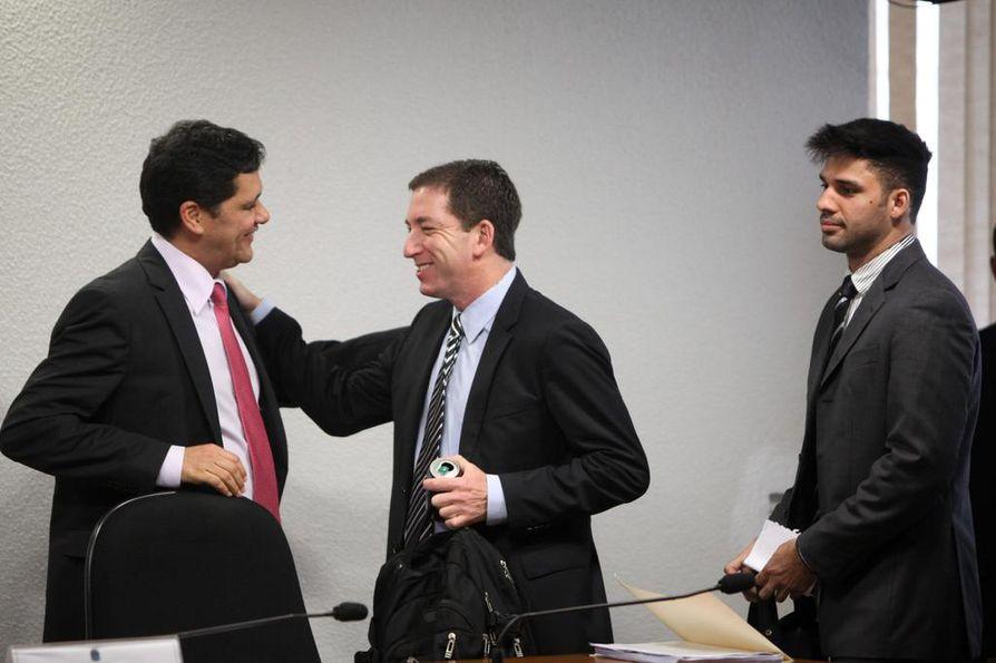 David Miranda (oik.) joutui valokeilaan, kun hän nousi kongressiin maanpakoon lähteneen tilalle. Kuvassa hän on miehensä Glenn Greenwaldin (kesk.) ja brasilialaisen senaattorin Ricardo Ferracon kanssa lokakuussa 2013.