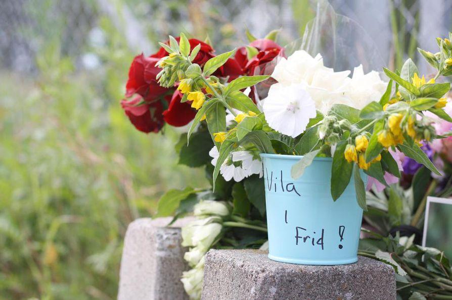 Ihmiset ovat tuoneet kukkia ja kynttilöitä kerhon edustalle.