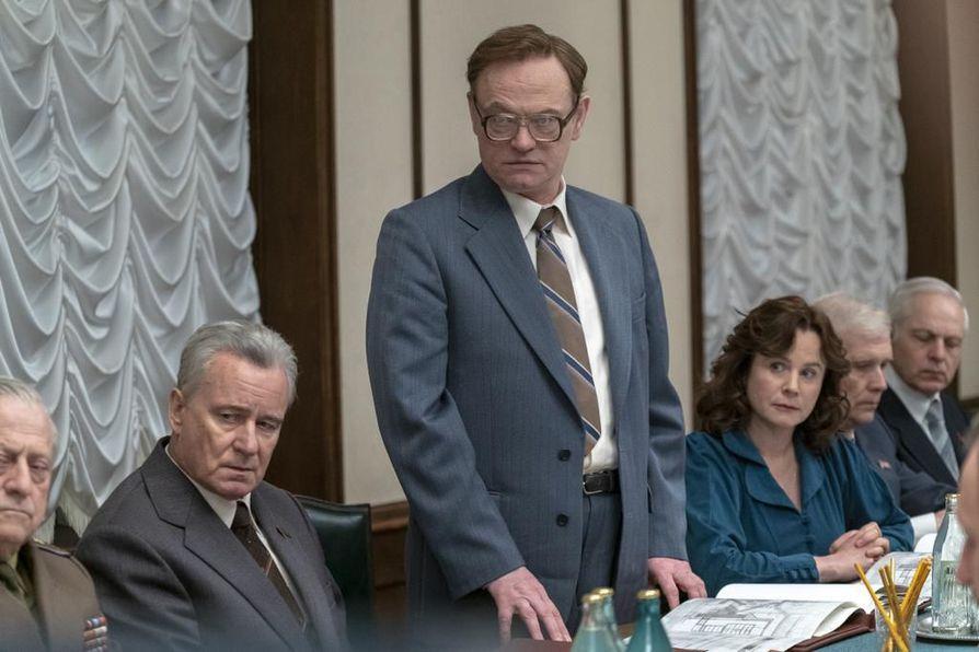 Valeri Legasov (Jared Harris) selvittää seisoaltaan Neuvostoliiton korkeimmalle johdolle, mitä Tshernobylissä on tapahtunut. Chernobyl-sarjan kohtauksessa Boris Shcherbina (Stella Skargård) istuu hänen vasemmalla ja Ulana Khomyuk (Emily Watson) oikealla puolellaan.