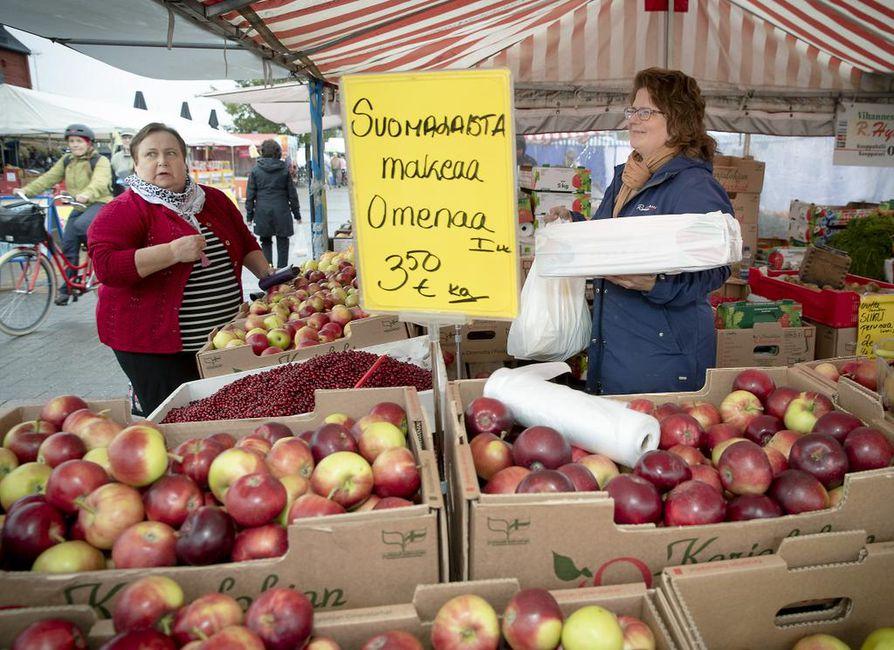 Irja Huttunen (vas.) sanoo olevansa onnellinen ostaja kauppatorin syysmarkkinoilla, jonne pitää päästä. Riikka Isohätälä myi hänelle omenoita.