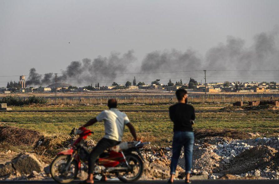 Ihmiset katselivat sunnuntaina Turkin ja Syyrian rajalla, kuinka Turkin pommittamista syyrialaiskohteista nousi savua.