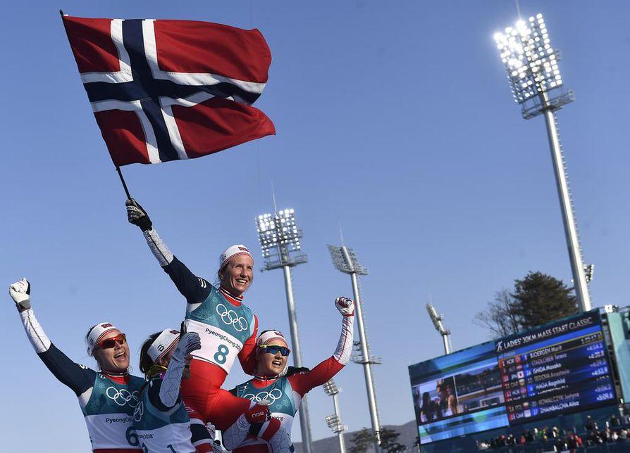 Joukkuekaverit nostivat Marit Björgenin kultatuoliin olympialaisten päätöskisan jälkeen.