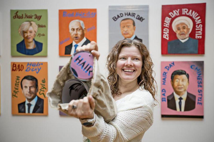 Museolehtori Laura Lampinen esittelee tehtäväpussin sisältöä. Tehtäviin kuuluu esimerkiksi piirtää Sauli Niinistölle                       hiukset ja etsiä yksityiskohtia Riiko Sakkisen feat. Louis Houenouden teoksesta Bad Hair Day Leaders (2018).