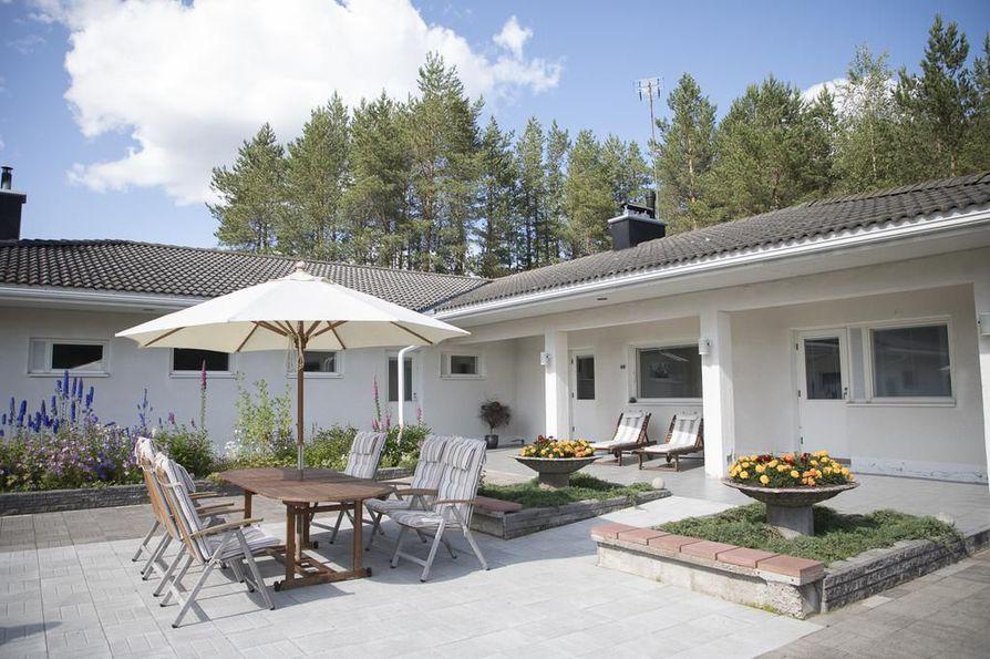 Avara piha on suojaisa ja lämpenee auringossa helposti. Isot, betoniset kukkajalustat ovat Pirjon tekemiä. Pihalamput ovat taas Väinön käsialaa.