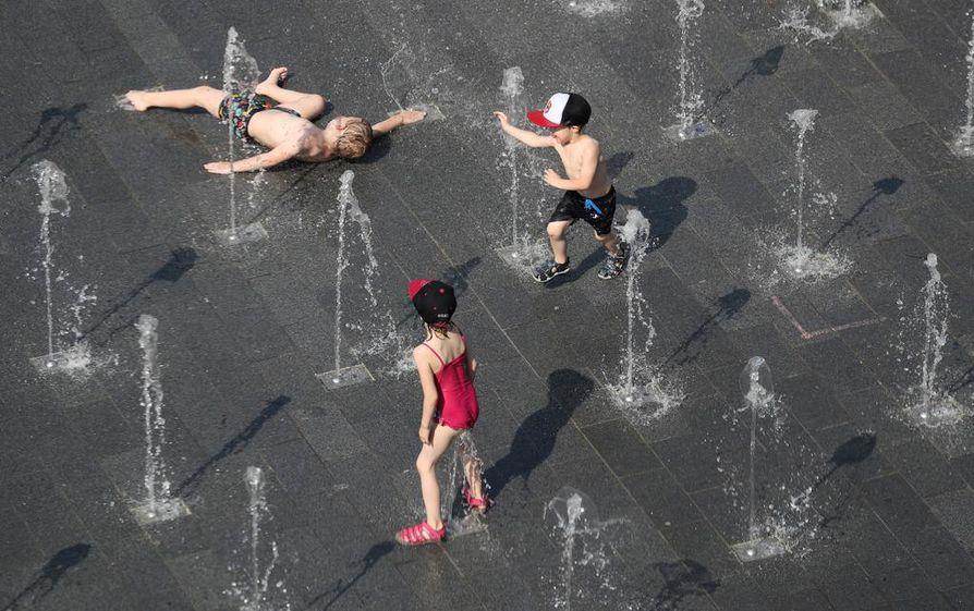 Lapset vilvoittelivat vedellä Saksan Duisburgissa keskiviikkona. Kesäkuun uusi lämpöennätys, 38,6 astetta rikkoutui Saksassa tiistaina.