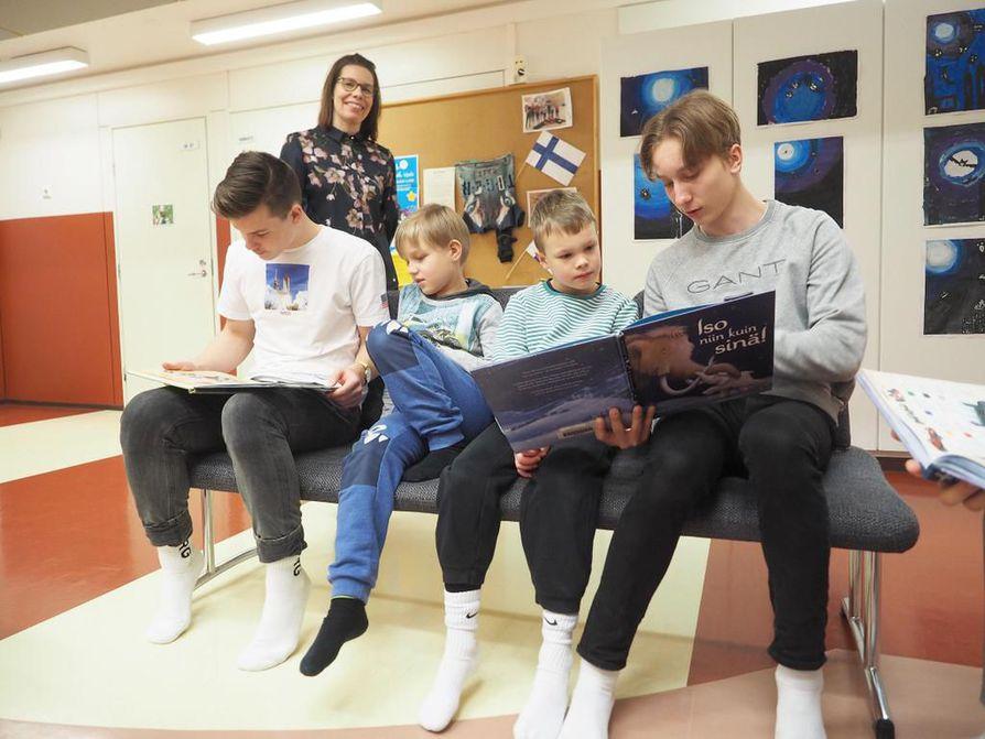 Tolpanniemen alakoulun ekaluokkalaiset aloittivat  koulupäivänsä lukemalla kirjoja yhdessä Kainuun ammattiopiston liiketalouden opiskelijoiden kanssa. Arttu Tyni (vas.) ja Jiri Hämeenniemi lukivat dinosauruksista ja Jimi Kyllönen (oik.) ja Antti-Pentti Määttä mammuteista. Pojat lukevat pojille -toiminnan ideoineelle opettaja Anu Vartiaiselle toiminta toi kutsun Linnan juhliin.