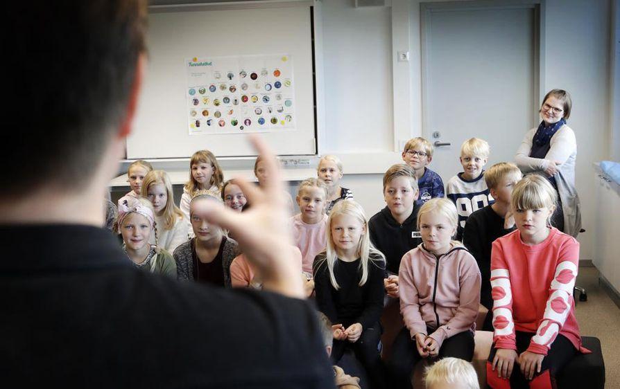 Ojanperän koulun neljäsluokkalaiset kuuntelivat kiinnostuneina kirjailijavieraan kertomusta, miten kirja syntyy. Taustalla opettaja, vararehtori ja kirjastovastaava Suvi Seppälä.