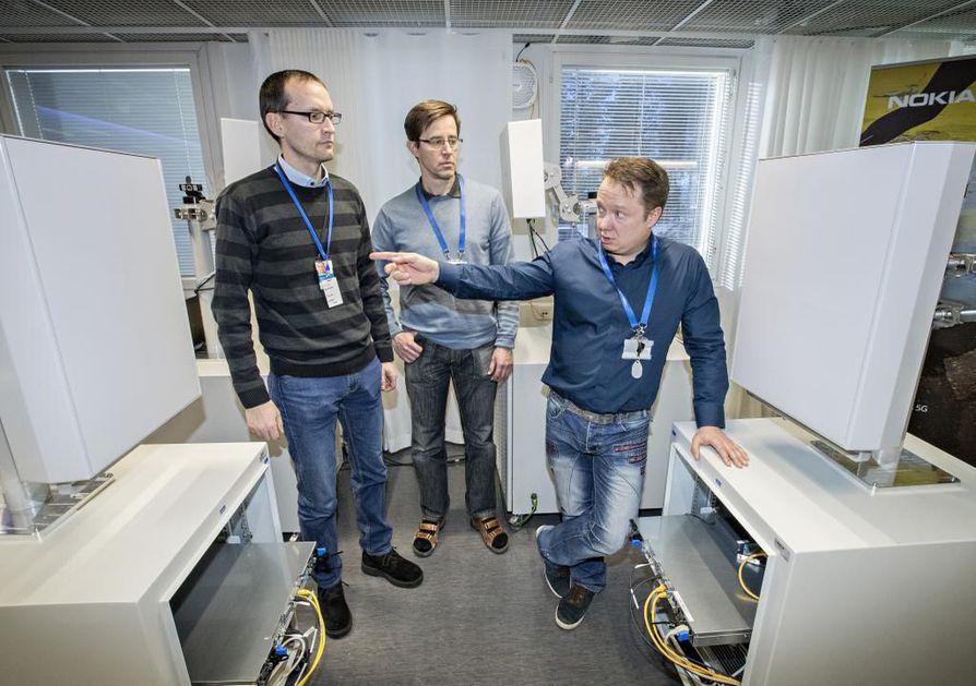 Nokian 5G-ohjelmajohtaja Aki Korvala (oik.), yliopiston 5G-projektipäällikkö Olli Liinamaa ja VTT:n projektipäällikkö Atso Hekkala toimivan 5G-demolaitteiston välissä. Näissä laitteissa on näkyvillä Nokian useiden vuosien työt 5G:n parissa alkaen vuoden 2011 ensimmäisistä patenteista.