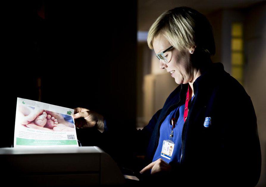 Kätilö Heta Ohtonen käyttää faksia OYSin synnytysosastolla.