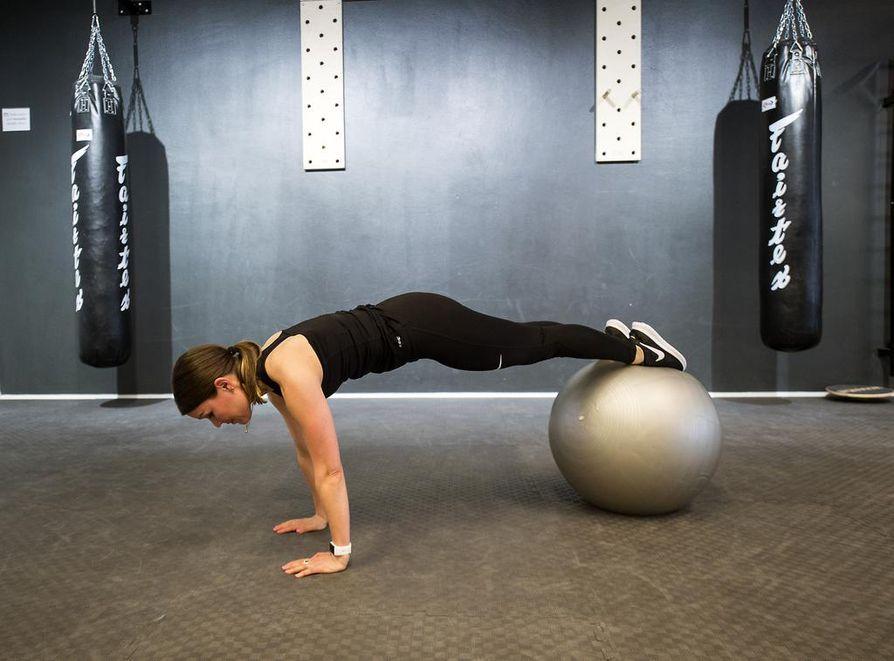 Aseta kädet hartioiden leveydelle, olkapäiden kanssa samaan linjaan. Nosta jalat pallon päälle ja kohota takapuoli kohti kattoa jalat suorina. Voit tehdä liikkeen myös pitämällä kädet kahvakuulien päällä, jolloin saat haastetta tasapainoon. Toista niin monta kertaa kuin pystyt.
