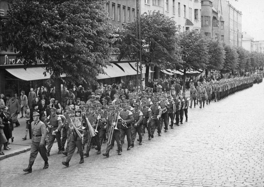 Tässä arkistokuvassa suomalaisten SS-vapaaehtoisten kulkue marssii Tampereen Hämeenkadulla 3.6.1943. Edessä kulkee saksalainen sotilassoittokunta.
