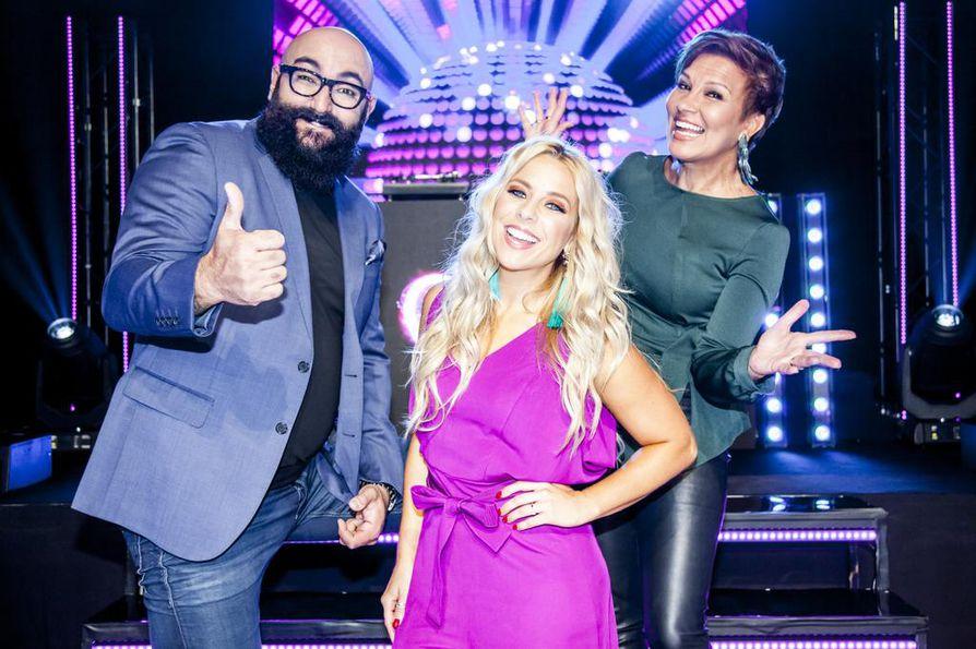 Hauskaa olla pitää. Tiimikapteenit Ali Jahangiri ja Arja Koriseva koettavat pitää tunnelman katossa TV5:n uudessa kilpailullisessa musiikkiviihdeohjelmassa. Keskellä säteilee juontaja Krista Siegfrieds.