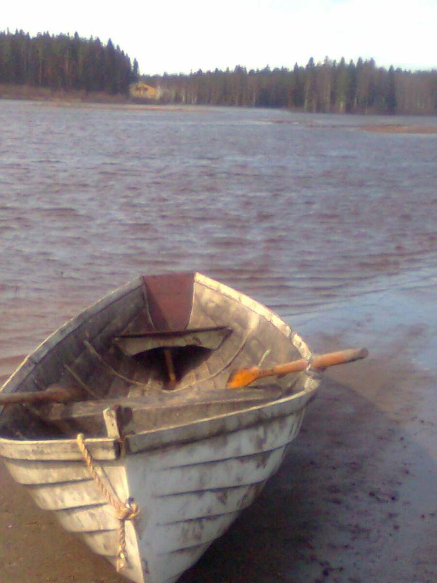"""Jukka Ojantakanen kulkee navetalleen soutuveneellä, koska tulva on katkaissut tien. Navetta siintää """"järven"""" toisella laidalla."""