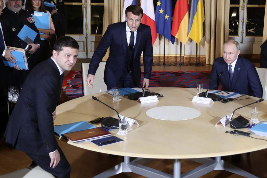 Ukrainan presidentti Volodymyr Zelenskyi (vas.) ja Ranskan presidentti Emmanuel Macron (kesk.) istahtivat maanantai-iltana Pariisissa samaan neuvottelupöytään Venäjän presidentti Vladimir Putinin kanssa. Tapaamisessa oli myös Saksan liittokansleri Angela Merkel.