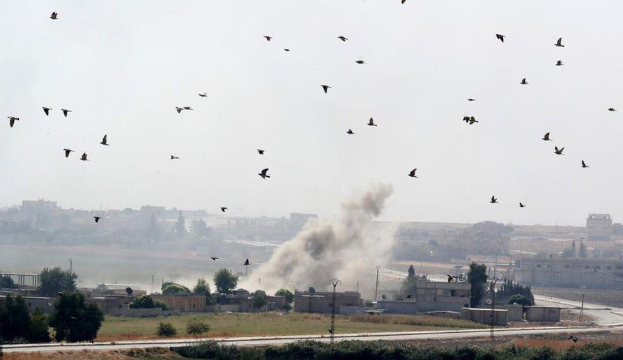 Koillis-Syyrian Ras al-Einin kaupungista nousi sankka savu Turkin pommitusten jäljiltä lauantaina. Kuva on otettu Turkin puolelta.