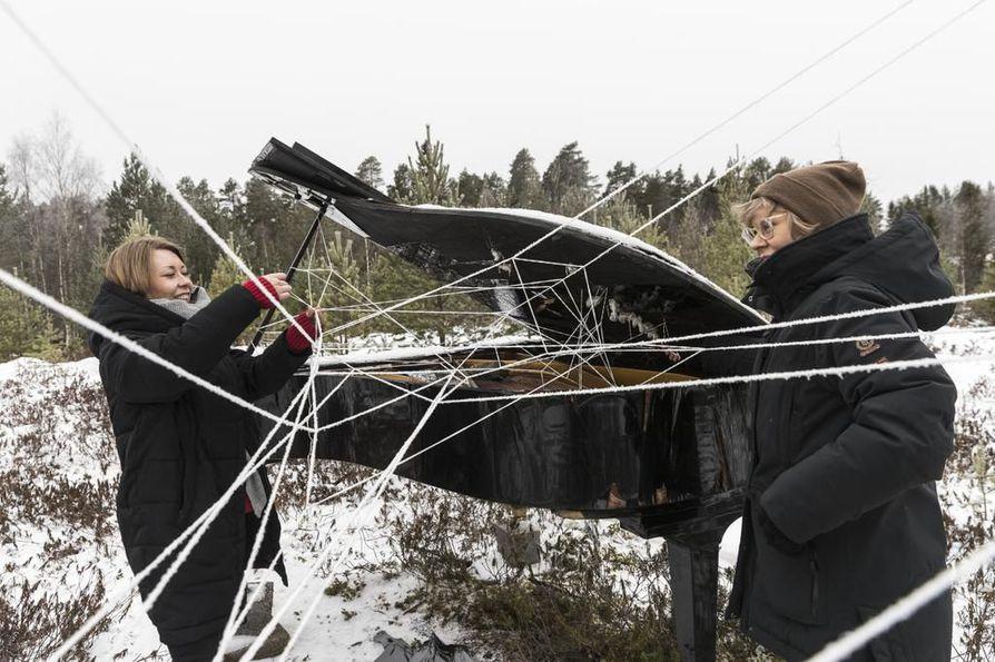 Muhoksen kulttuurituottaja Taija Jyrkäs (vas.) ja Lemmenpolun valotapahtuman taiteellinen johtaja Jenni Kinnunen solmivat nyörejä flyygeliin, josta on tulossa Montan vene.