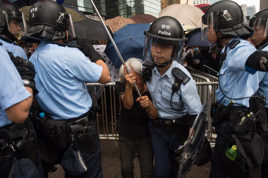 Poliisi hätisteli mielensoittajaa kauemmaksi Hongkongin itsehallintoparlamentin edustalta keskiviikkona.