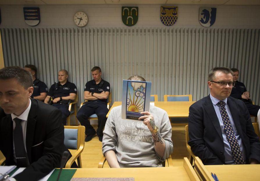 Murhasyytetyt peittivät  kasvonsa käräjäoikeudessa. Vuonna 1995 syntynyttä miestä avustaa asianajaja Markus Pöhö (vas.). Oikella puolella istuu toista murhasta syytettyä avustava varatuomari Tuukka Tieksola.  Kaikkiaan kolmelle miehelle vaaditaan rangaistusta murhasta.