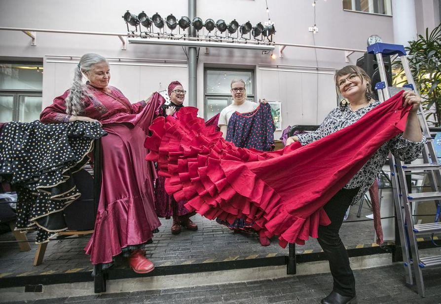Kulttuuritalo Valveella on esillä juhlanäyttely ¡Flamenco, Oulu! Näyttelyä olivat maanantaina ripustamassa Päivyt Huttu-Hiltunen (vas.), Leena Suoranta, Minna Järvelä ja Pirjo Lempeä, joka heiluttaa bata de cola -hametta. –¿Itse olen ommellut siihen kaikki röyhelöt ja frillat. Ilman flamencoa elämästä puuttuisi iloa ja ruusuja, hikeä ja kärsimystä, Pirjo Lempeä sanoo.