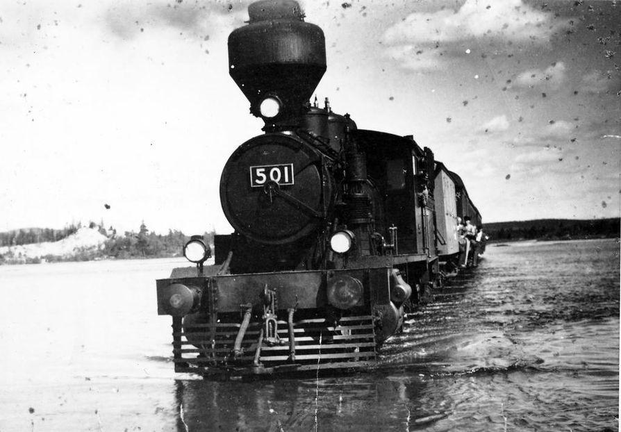 """Kesän korvalla 1949 junaliikenteen tilapäinen pukkisilta Ounasjoen suulla oli saatu jo valmiiksi, kunnes tulva peitti sen. Näin Kemijärveltä tullut juna """"kahlasi"""" joen poikki."""