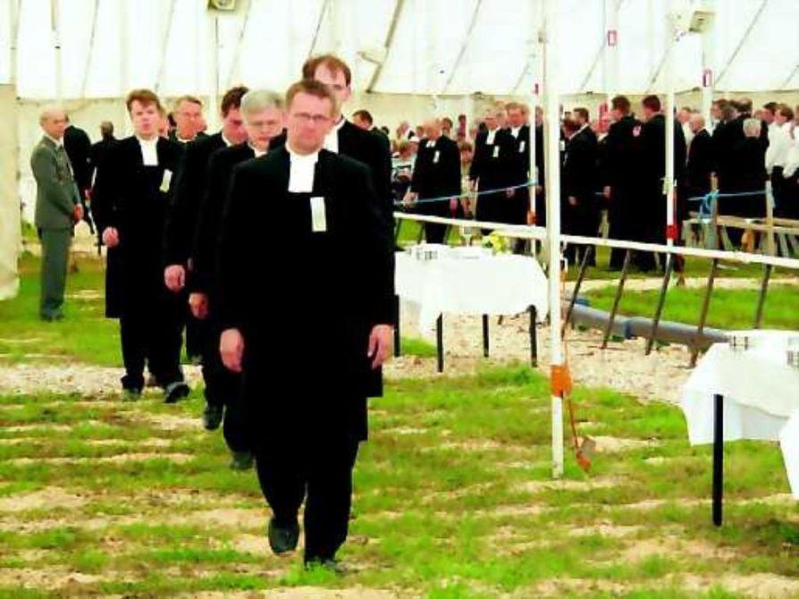 Miehinen rivistö. Suviseurojen ehtoollista jakamassa on viitisenkymmentä pappia. Liikkeen periaatteiden mukaisesti he kaikki ovat miehiä.