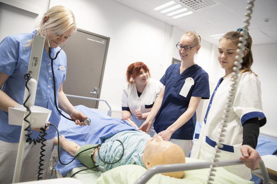 Lähihoitajaksi opiskelevat Johanna Stenroos (vasemmalla), Kamilla Lehtonen, Henna-Sofia Pohjola ja Nella Agge harjoittelevat hoitotoimia nuken kanssa.