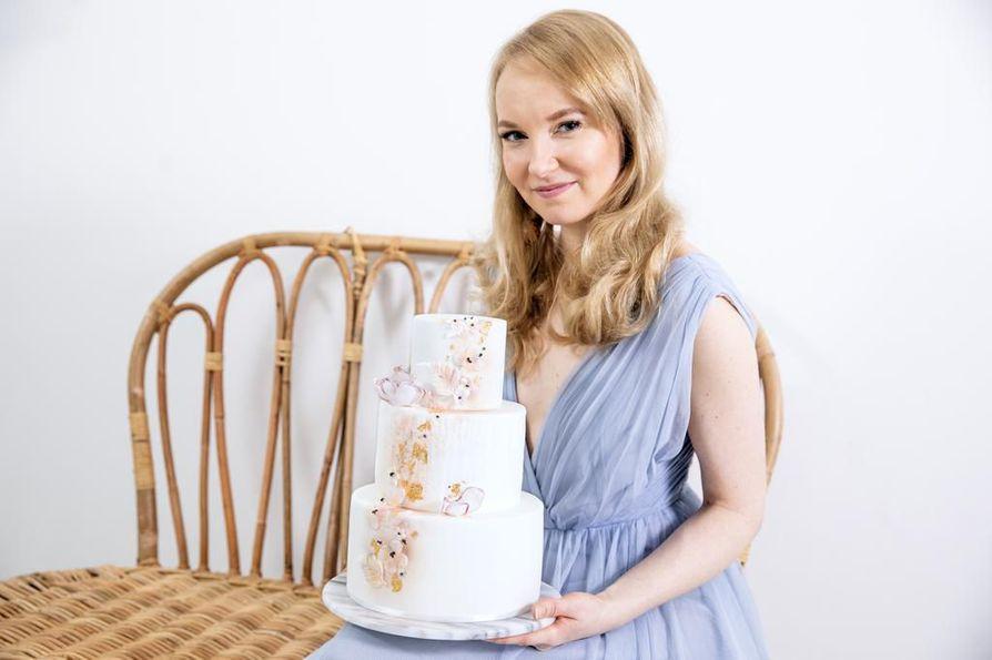 Kakkutaiteilija kantaa kakun olohuoneeseen ja poseeraa tottuneesti sen kanssa rottinkisohvalla. Kaikki on ajateltu viimeisen päälle, kun kyseessä on brändi nimeltä Emma Ivane.