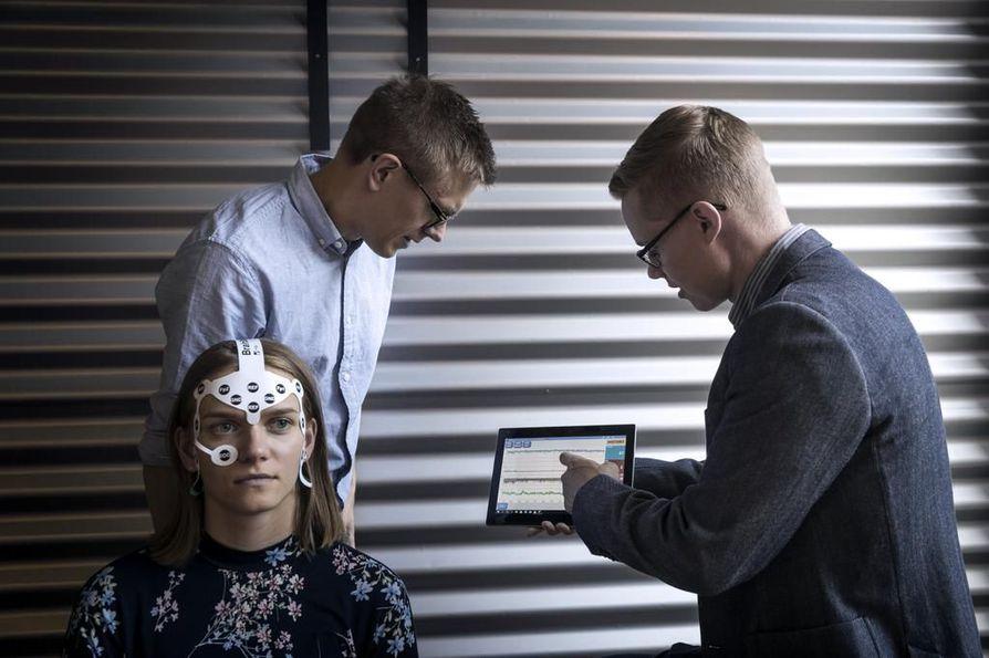 Cerenionin perustajiin kuuluvat Timo Koskela (vas.) ja Jukka Kortelainen esittelevät yrityksen ohjelmiston käyttöä aivosähkökäyrän tulkinnassa. Mittalaite päässään on ohjelmistokehittäjä Erika Niemelä. Analyysin tiedot piirtyvät tabletin ruudulle. Yksi numero kertoo, onko aivosähkökäyrä kunnossa.