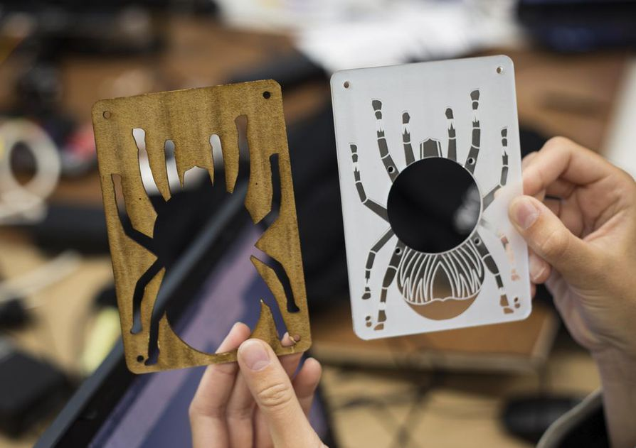 Koodikärpissä tehdään myös tuotekehitystä. Kuvassa Tevo Tarantula -3D-printteriin itse tehty emolevysuoja, joka on rasteroitu ja leikattu laserleikkurilla. Vasemmalla varhainen prototyyppi, oikealla viimeisin malli.