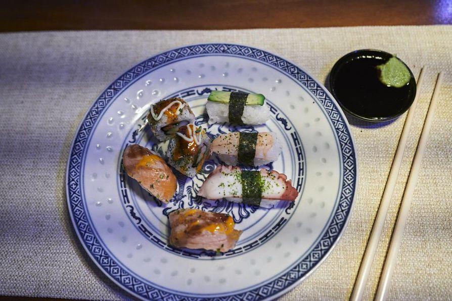 Hai Longin sushibuffetissa on tarjolla on erilaisia kala- merenelävä- ja kasvissusheja, joita on koristeltu ja maustettu erilaisin kastikkein.