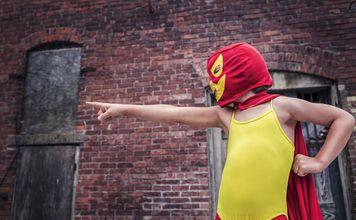 Supersankariasuun pukeutunut lapsi valmiina toimimaan.