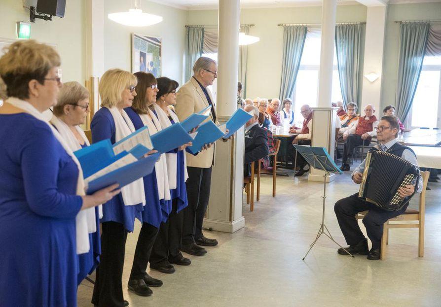 Oulun työväen eläkeläisten lauluryhmä Sinitaivas harjoittelee Aleksinkulmassa. Säestäjänä on Hannes Leskinen.