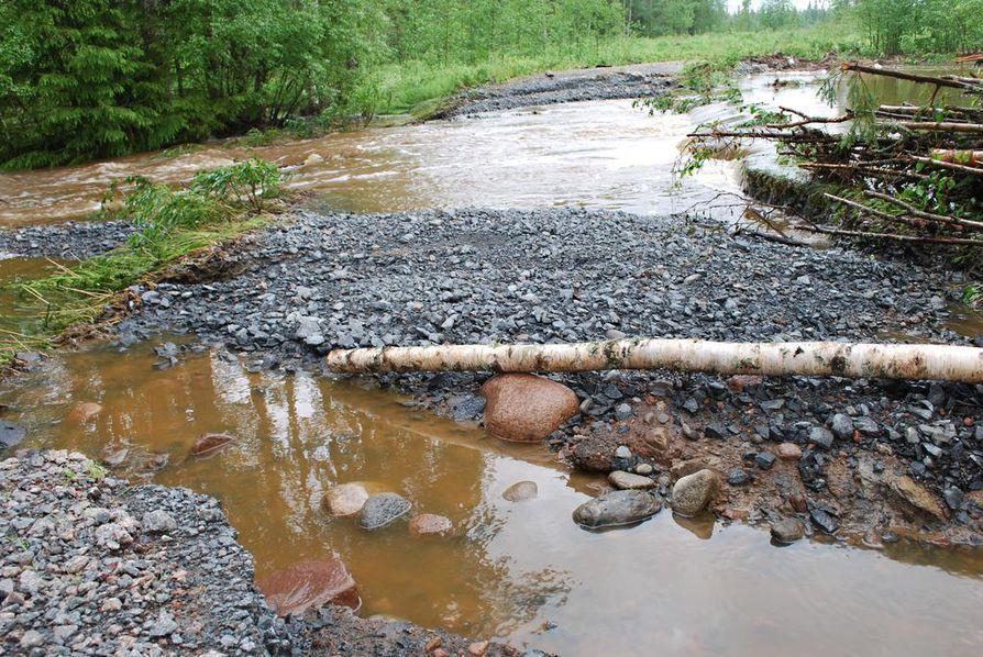 Matkanivassa olevan Knuutilantien varressa vesi virtaa vuolaasti pikkuteiden yli.