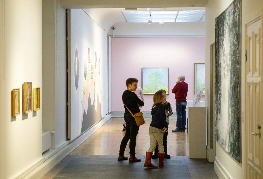 Katariina Mankinen sekä Maija Mankinen, 9, ja Niilo Ronkainen, 9, tutkivat porukalla Ellen Thesleffin maalauksia.